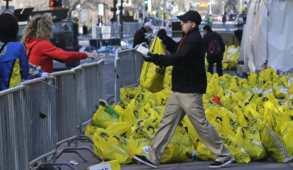 A worker returns a bag containing a runner's personal effects near the finish line of the Boston Marathon on April 16, 2013, after bombs placed in backpacks killed three people.