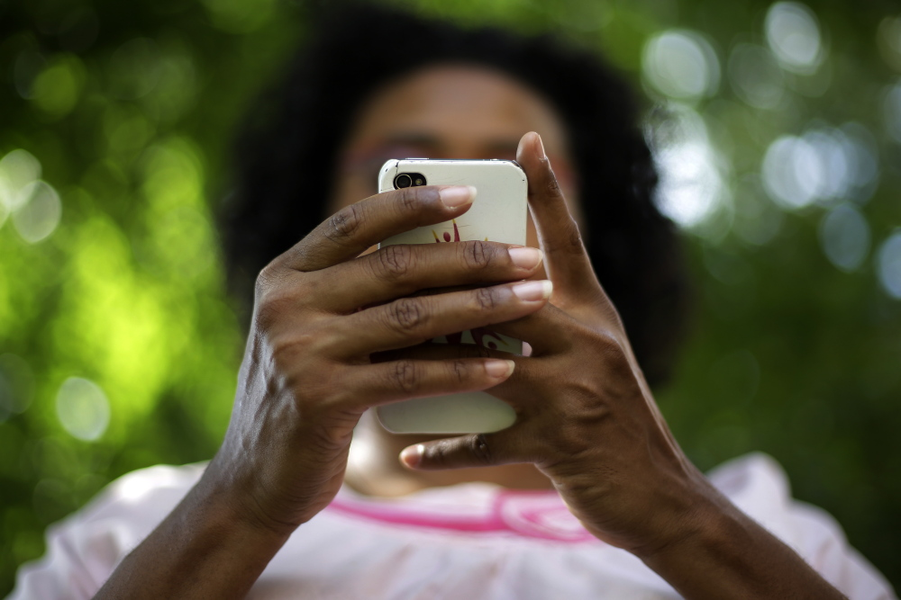 """Kimberly C. Ellis tweets at Freedom Corner in the Hill District of Pittsburgh. Ellis, who has a doctorate in American and Africana Studies, is studying Black Twitter for her upcoming book, """"The Bombastic Brilliance of Black Twitter."""""""