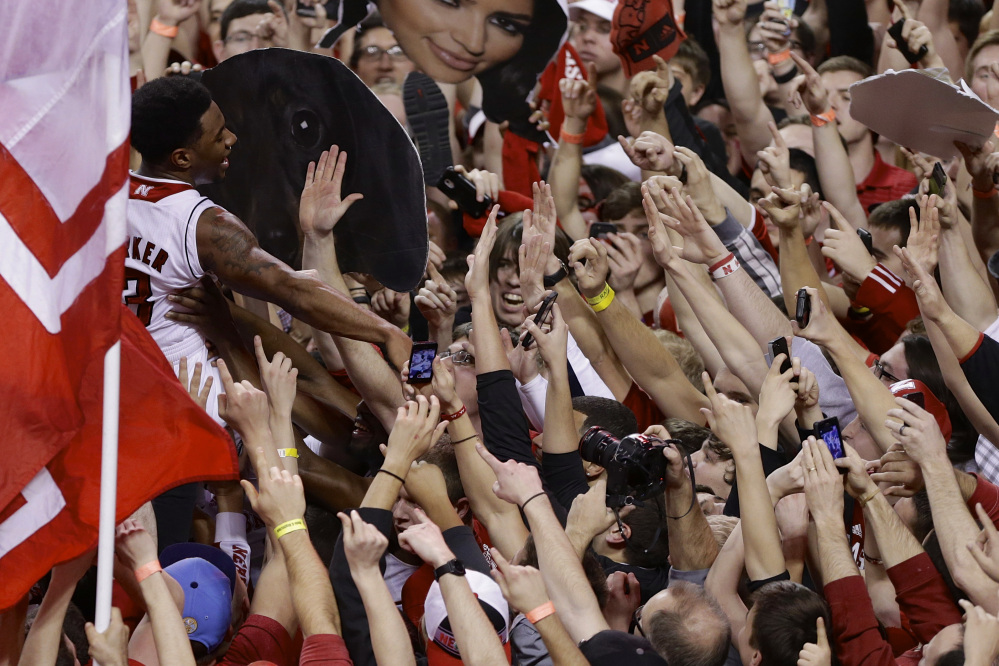 Nebraska's Benny Parker (3) is carried on the shoulders of fans who stormed the court following a game against Wisconsin in Lincoln, Neb., on Sunday. Nebraska won 77-68.