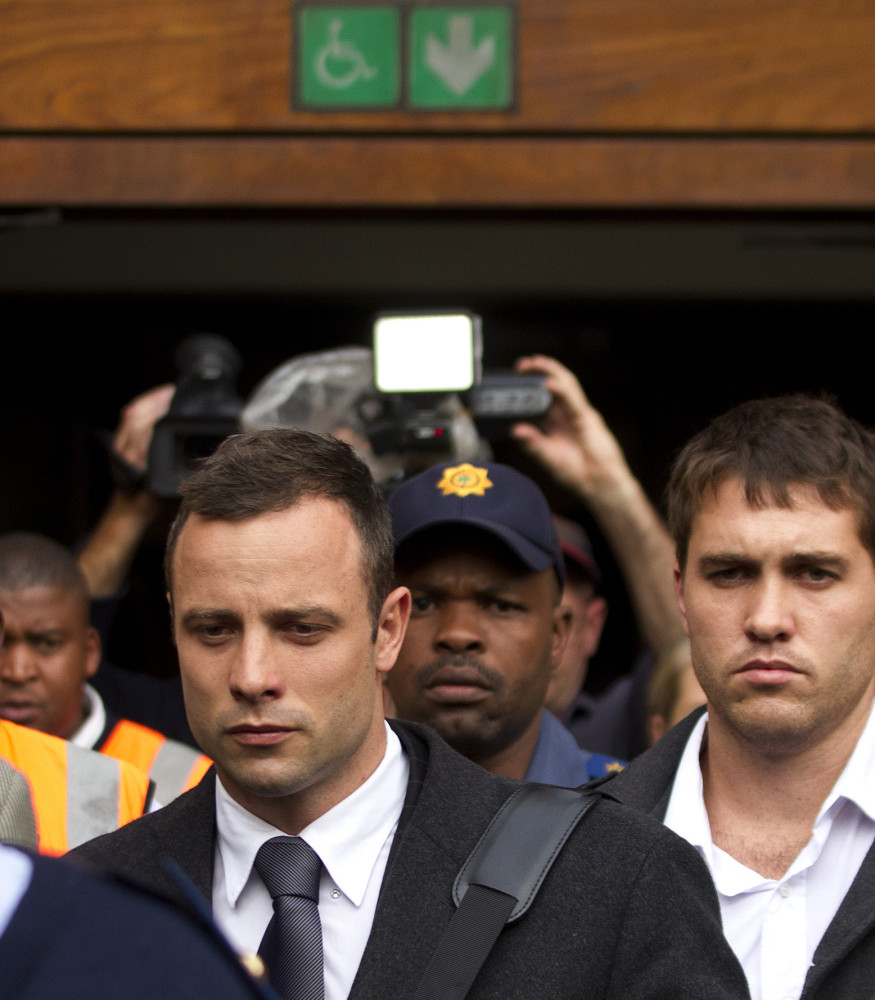 Oscar Pistorius, left, leaves the high court Tuesday in Pretoria, South Africa, Tuesday. He is charged with murder in the shooting death of his girlfriend in 2013.