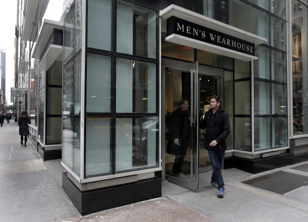 Two men exit a Men's Wearhouse store in New York last week. Men's Wearhouse will buy Jos. A. Bank Clothiers Inc. for $65 a share, the company announced Monday.