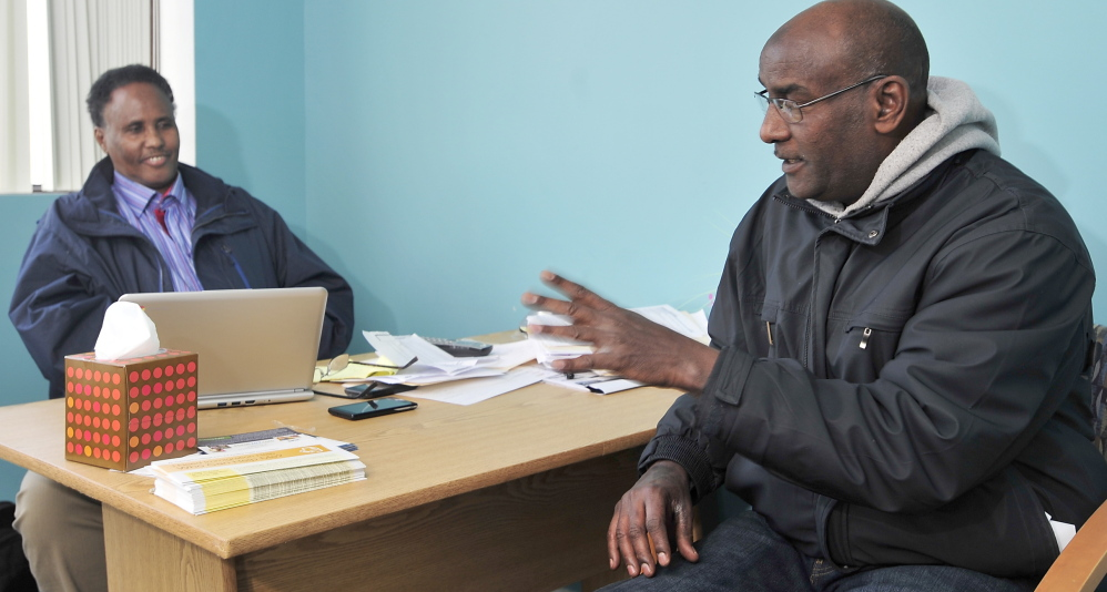 Community Health Outreach Worker Mohammed Hassan, left, explains the Affordable Care Act to Mohamed Obsieh, an asylum-seeker from Djibouti who said he would like coverage if he can afford it.