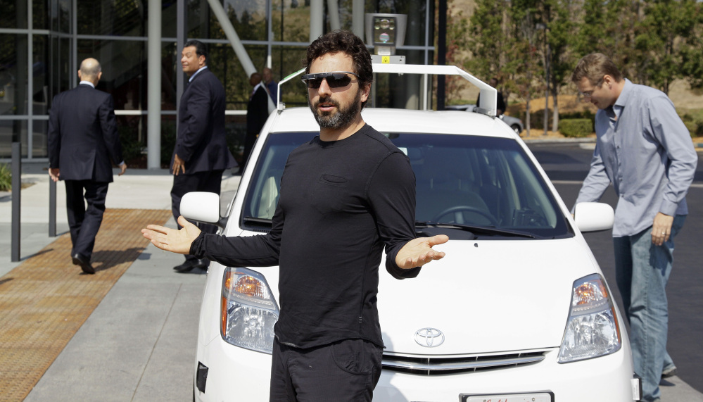 Google Inc. co-founder Sergey Brin exits a driverless car with California Gov. Edmund G. Brown Jr., walking away at left, as they head to the 2012 signing of a bill mandating that the state develop rules on public operation of the vehicles.