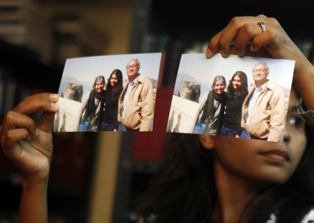 "Photographs showing one of the passengers of the missing Malaysian Airlines aircraft Chandrika Sharma, left, her husband, Narendran, and daughter Meghna, are displayed during a news conference in Chennai, India, Wednesday. Narendran criticized the Indian government for its ""silence"" and said no government official has contacted the family about the incident, according to a local news agency."