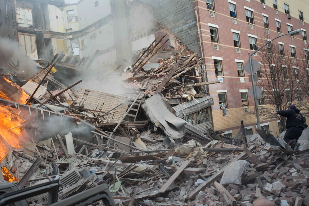 Emergency workers respond to the scene of an explosion that leveled two apartment buildings in the East Harlem neighborhood of New York City on Wednesday.