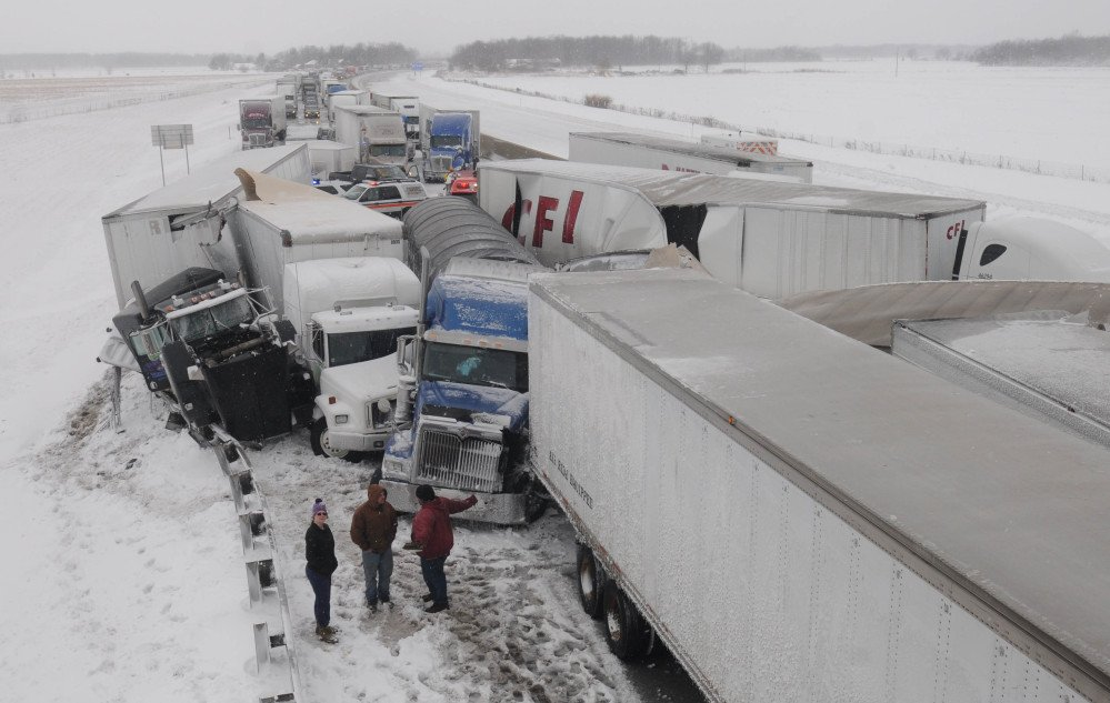 Truck drivers talk among themselves at the scene of an accident on the Ohio Turnpike northeast of Clyde, Ohio, after more than 50 vehicles crashed Wednesday. It was expected to be days before the road could be cleared.