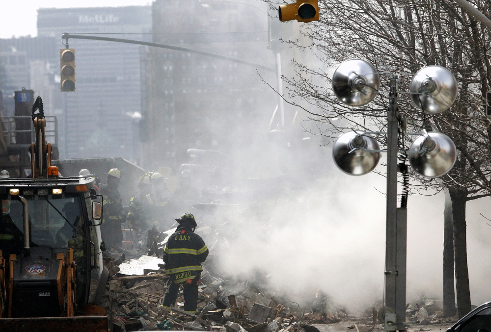 Smoke rises from debris as a firefighter stands near rubble a day after a gas leak-triggered explosion, on Thursday in East Harlem, New York. Rescuers working amid gusty winds, cold temperatures and billowing smoke continued to search for five people still unaccounted for Thursday.