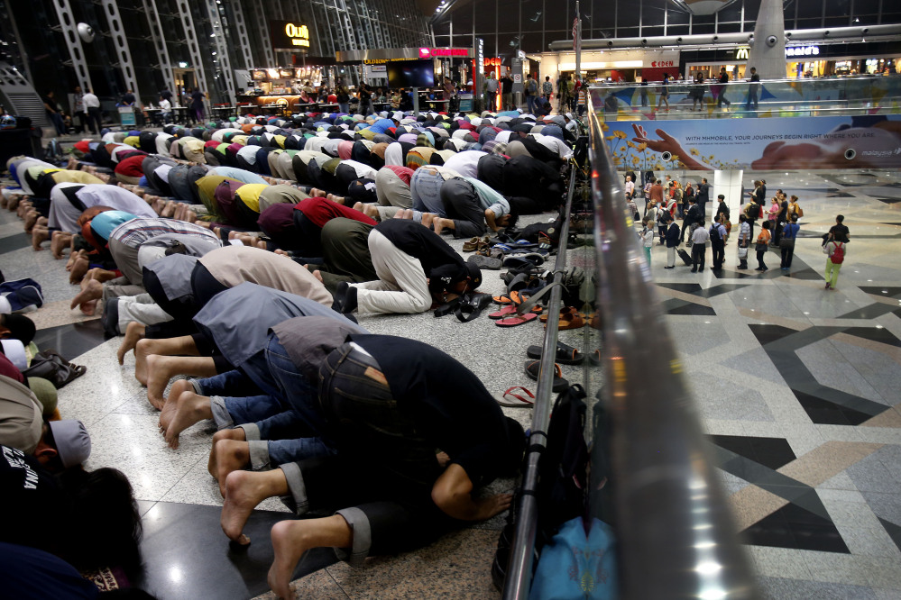 Muslim men offer prayers at the Kuala Lumpur International Airport for the missing Malaysia Airlines jetliner MH370 on Thusday, while on a level down, travelers queue up at immigration checkpoints.