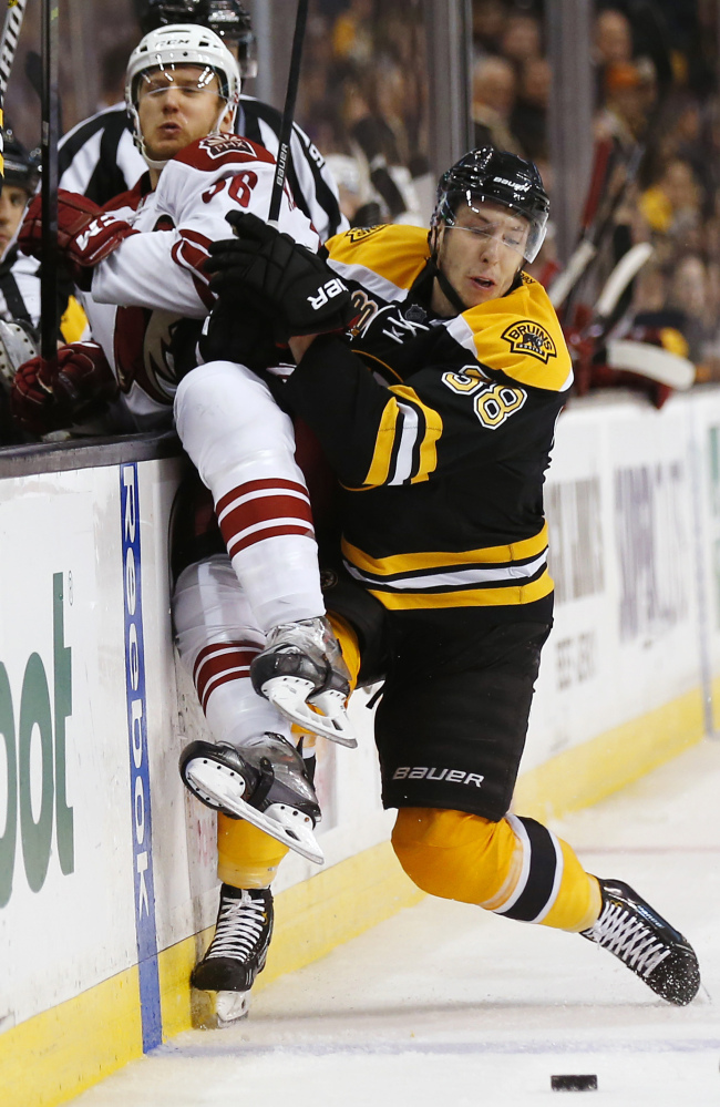 Boston Bruins' Jordan Caron checks Phoenix Coyotes' Rob Klinkhammer into the boards in the third period Thursday.