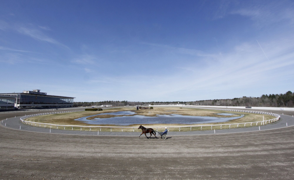 In this 2010 file photo, a horseman jogs around the half-mile track at Scarborough Downs in Scarborough. Opponents of slot machines at Scarborough Downs hope third time's not a charm.