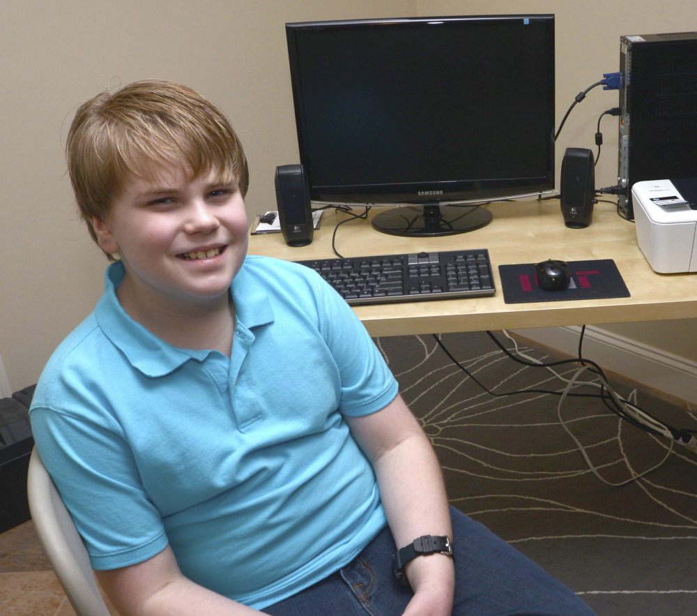 Ryan Gendron, 11, poses at his computer desk in Newburyport, Mass. Ryan and his father sell low-cost computer bundles to families in need.