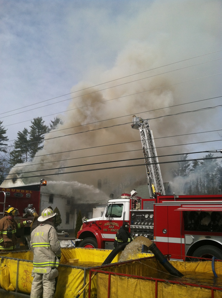Firefighters pump water to fight a house fire in Arundel on Friday.