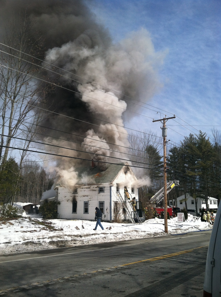 Firefighters battle a fire at 728 Alfred Road in Arundel across from Ledge Cliff Drive on Friday morning.