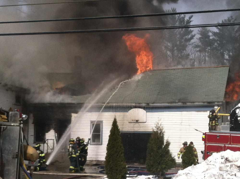 Firefighters battle a fire at a house on Route 111 in Arundel.
