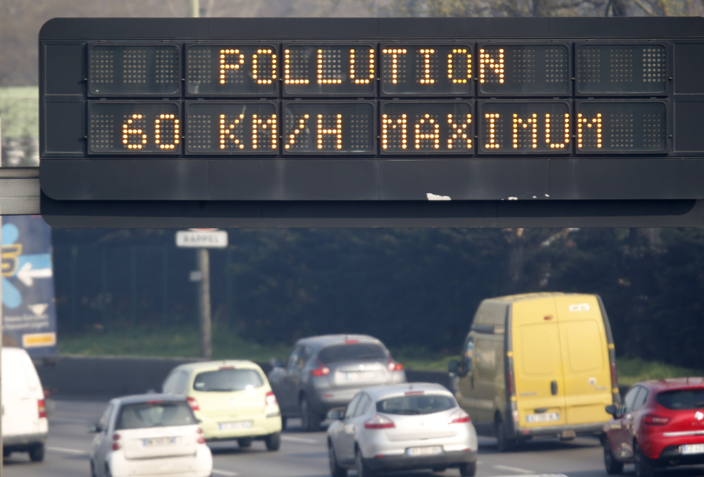 "An electronic road sign reads ""Pollution, speed limit 60 kms"" on the Paris ring road Friday. Residents and visitors faced a dangerous dose of particles from smog."