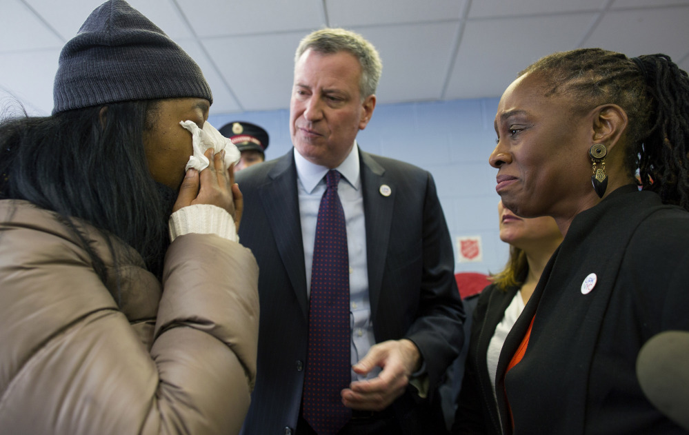 Aisha Watts, left, who was displaced after a gas explosion leveled two buildings in the East Harlem neighborhood of New York City on Wednesday, cries as she talks with New York City Mayor Bill de Blasio and his wife Chirlane McCray, at a Red Cross shelter being operated by the Salvation Army in New York on Friday.