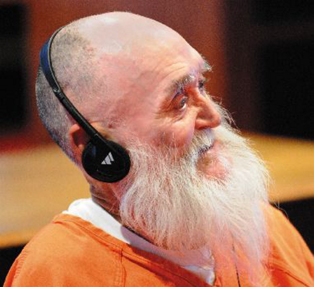 Gary Raub, wearing headphones to hear court proceedings, will stand trial in August in the killing of his former landlady in 1976.