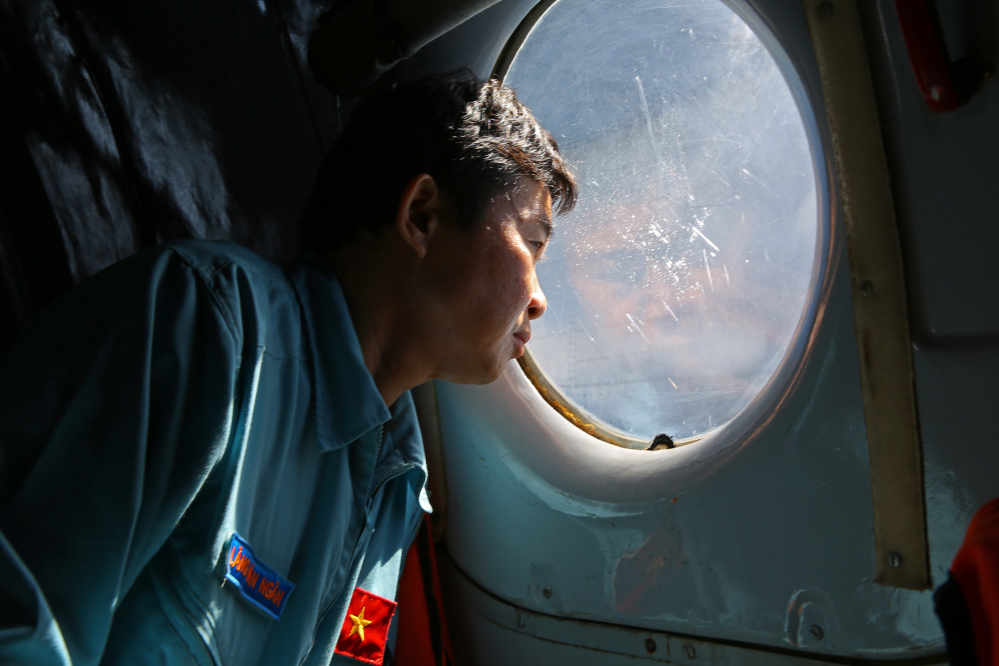 Officer Lang Van Ngan of the Vietnam Air Force looks out the window of an AN-26 Soviet made aircraft during a search operation for the missing Malaysia Airlines flight MH370 plane over the southern sea between Vietnam and Malaysia Friday.