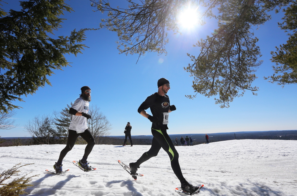 As the sun blazes their path, Trail Monsters Ian Parlin, right, and Tyler Lupien run along the summit of Bradbury Mountain State Park last Sunday.