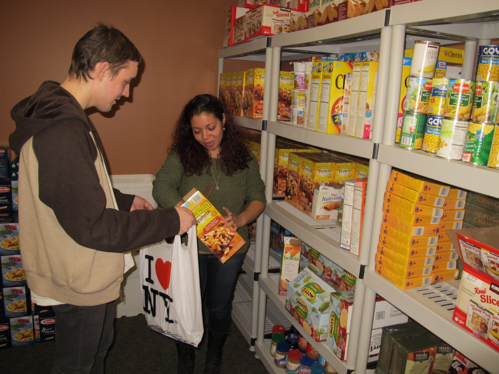 Stony Brook University students Ruby Escalera-Nater and Will Addison fill a bag of food to give to guests at the college's recently opened food pantry. Officials say there are a growing number of food pantries opening on college campuses across the country to assist students contending with rising education costs.