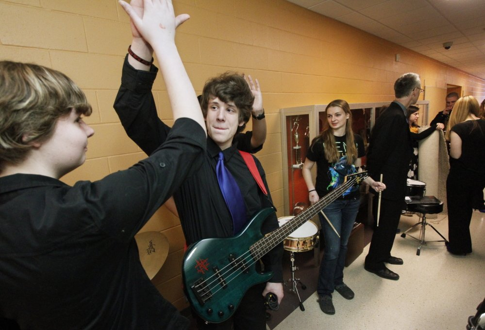 Westbrook High School jazz band members Sydney Marchand-Sirois and Milo Brooking high-five backstage before going out to compete at Hampden Academy.