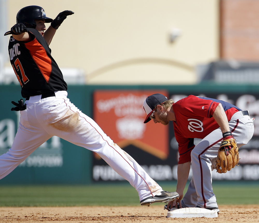 Miami's Brian Bogusevic, left, stretches for second base but is called out as Washington's Mike Fontenot did come up with the ball in a spring training game Saturday at Jupiter, Fla.
