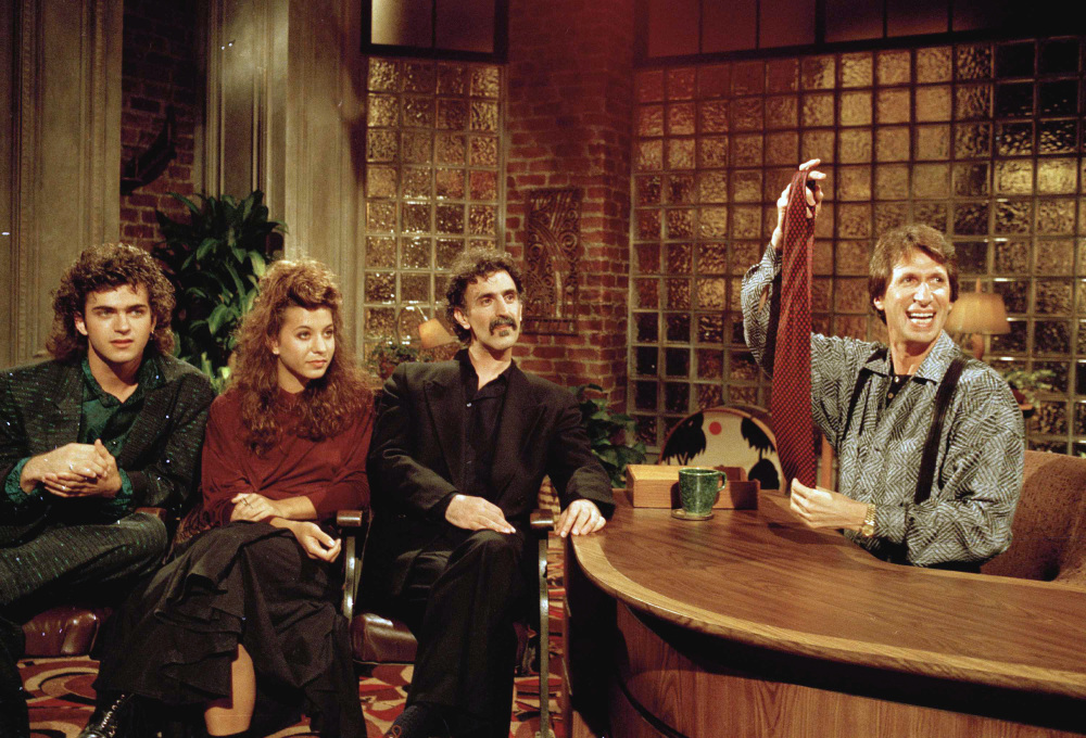"""Comedian David Brenner hosts avant garde fusion musician Frank Zappa, center, and his children, Dweezil, left, and Moon Unit during a taping of his """"Nightlife"""" talk show in New York in 1986."""