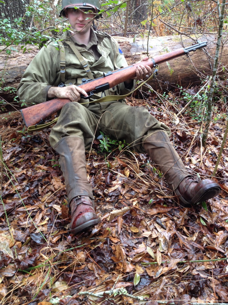 Re-enactor Justin Prejean plays a D-Day soldier preparing to tend to his wounded foot.