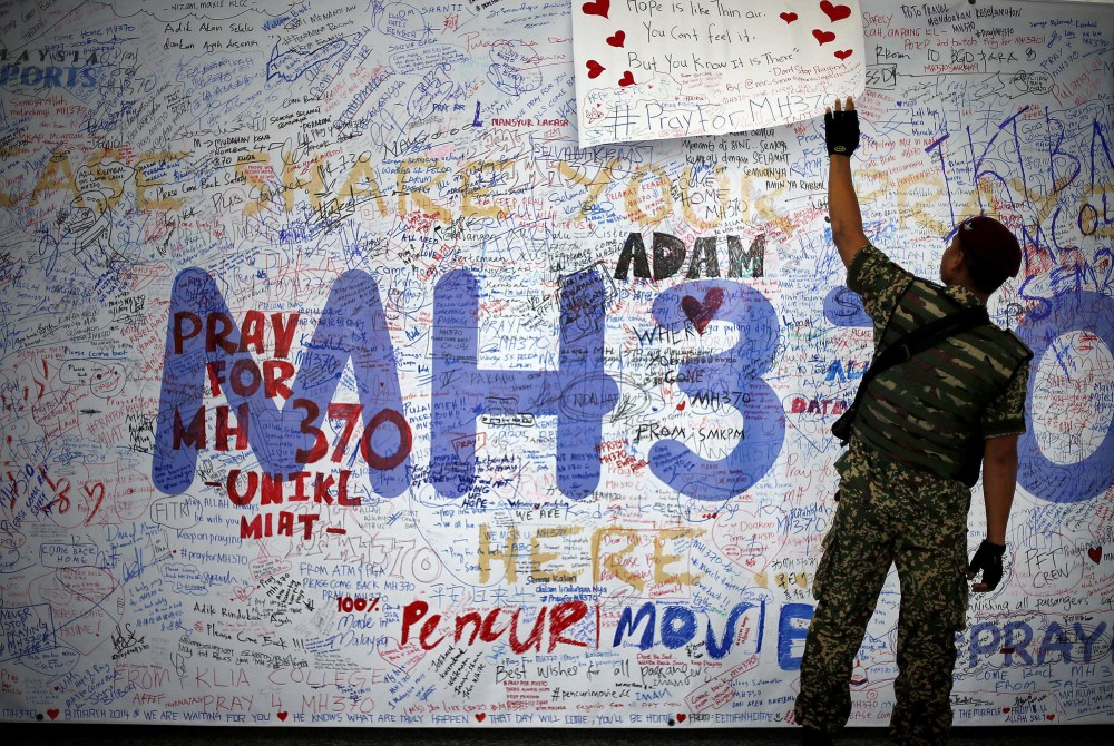 A Malaysian soldier patroling the Kuala Lumpur International Airport on Sunday reads a dedication board with messages for people involved with the missing Malaysia Airlines jetliner MH370.