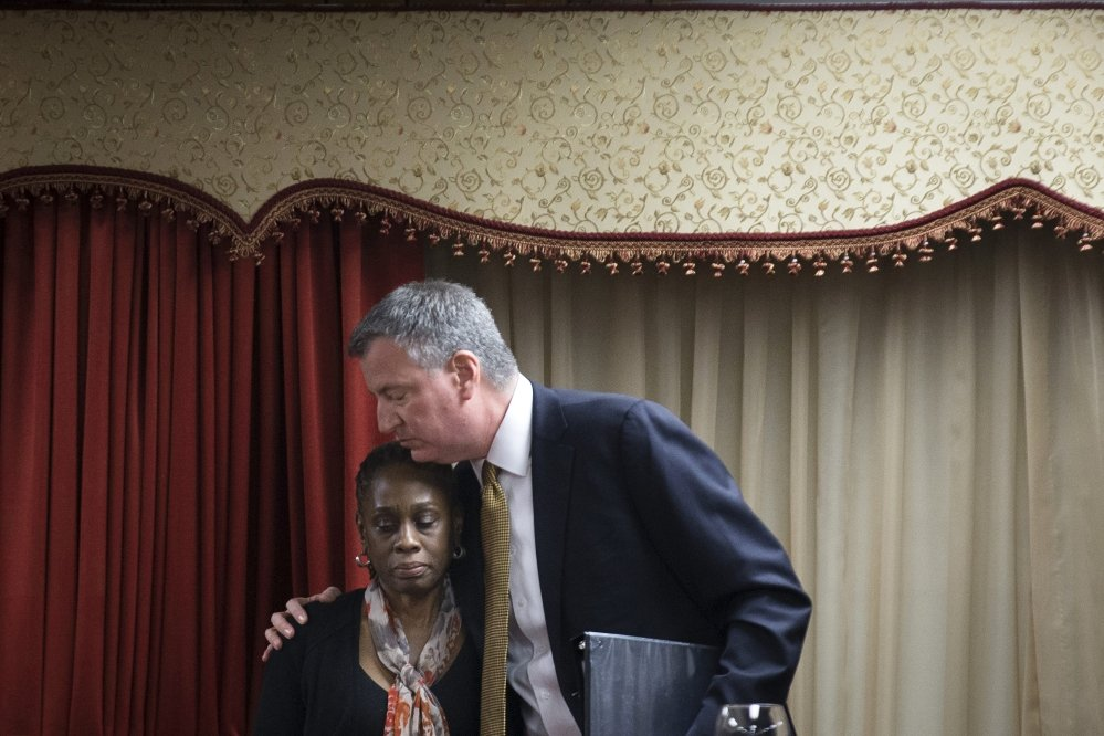 New York City Mayor Bill de Blasio, right, hugs his wife Chirlane McCray after speaking at the Church of God of Third Avenue as the congregation welcomed members of the Spanish Christian Church after the church was destroyed by Wednesday's explosion in the East Harlem neighborhood of New York, Sunday.