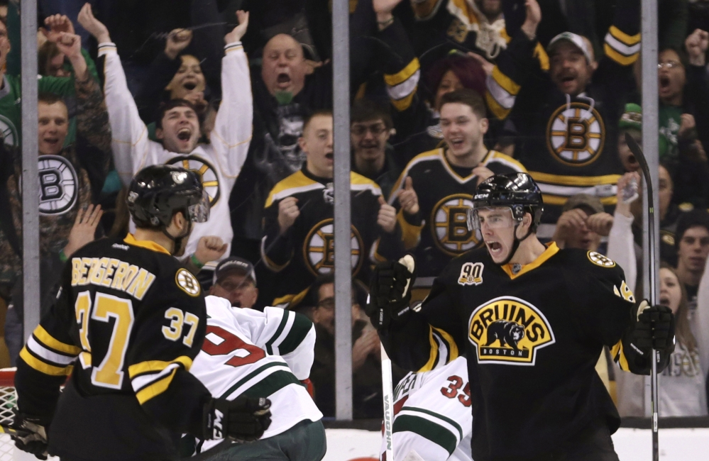 Boston Bruins fans celebrate with right wing Reilly Smith, right, after his goal during the third period of an NHL hockey game against the Minnesota Wild, Monday, March 17, 2014, in Boston. The Bruins defeated the Wild 4-1. (AP Photo/Charles Krupa)