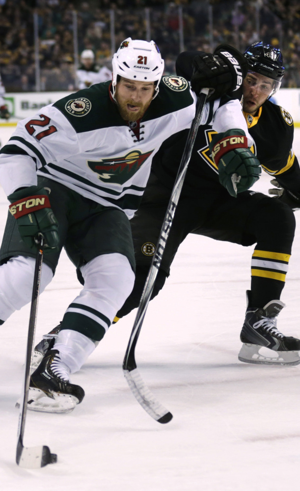 Boston Bruins center Gregory Campbell, right, chases Minnesota Wild center Kyle Brodziak (21) during the first period of an NHL hockey game, Monday, March 17, 2014, in Boston. (AP Photo/Charles Krupa)