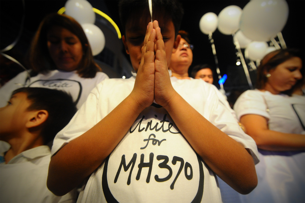 A young Malaysian boy prays, at an event for the missing Malaysia Airline, MH370, at a shopping mall, in Petaling Jaya, on the outskirts of Kuala Lumpur, Malaysia, Tuesday, March 18, 2014. A coalition of 26 countries, including Thailand, are looking for Malaysia Airlines Flight 370, which vanished March 8 with 239 people aboard on a night flight from Kuala Lumpur to Beijing. Search crews are scouring two giant arcs of territory amounting to the size of Australia ó half of it in the remote seas of the southern Indian Ocean.