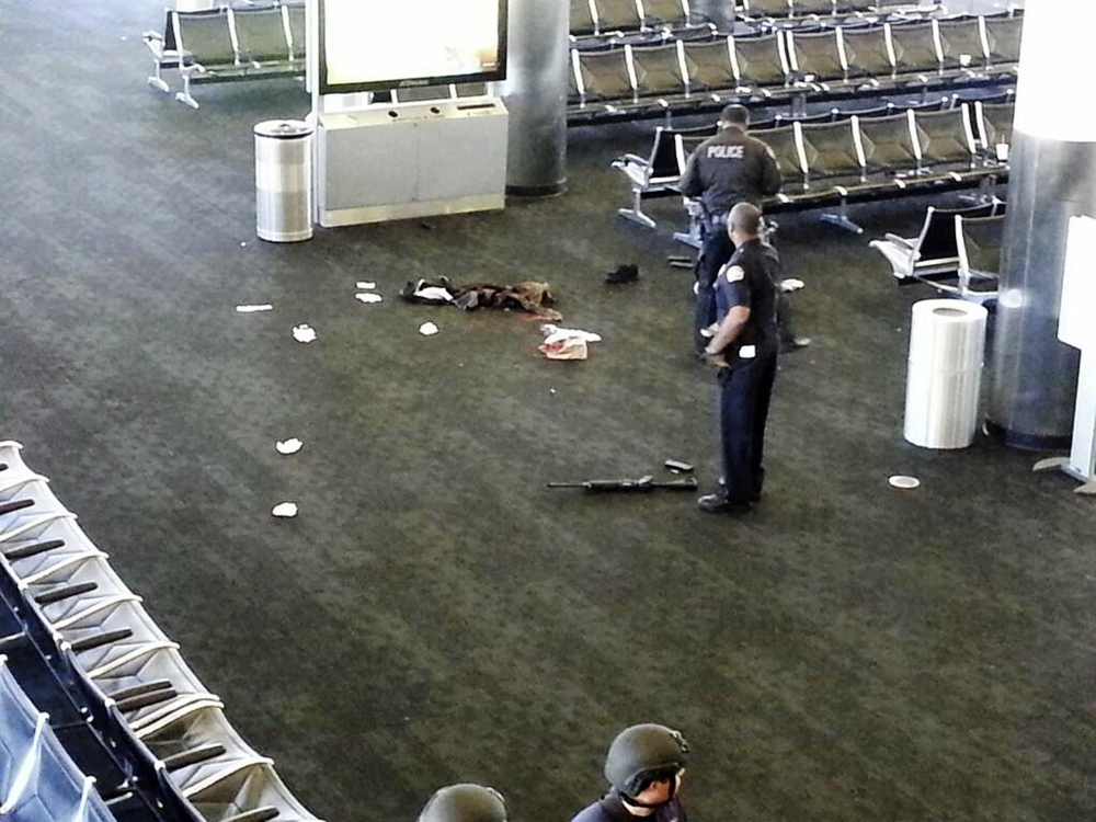 In this Nov. 1, 2013 file photo police officers stand near a weapon at the Los Angeles International Airport after a gunman opened fire in the terminal, killing one person and wounding several others. Thousands of Los Angeles International Airport workers had no idea what to do when a gunman opened fire last year or how to help because they were inadequately trained to deal with an emergency.