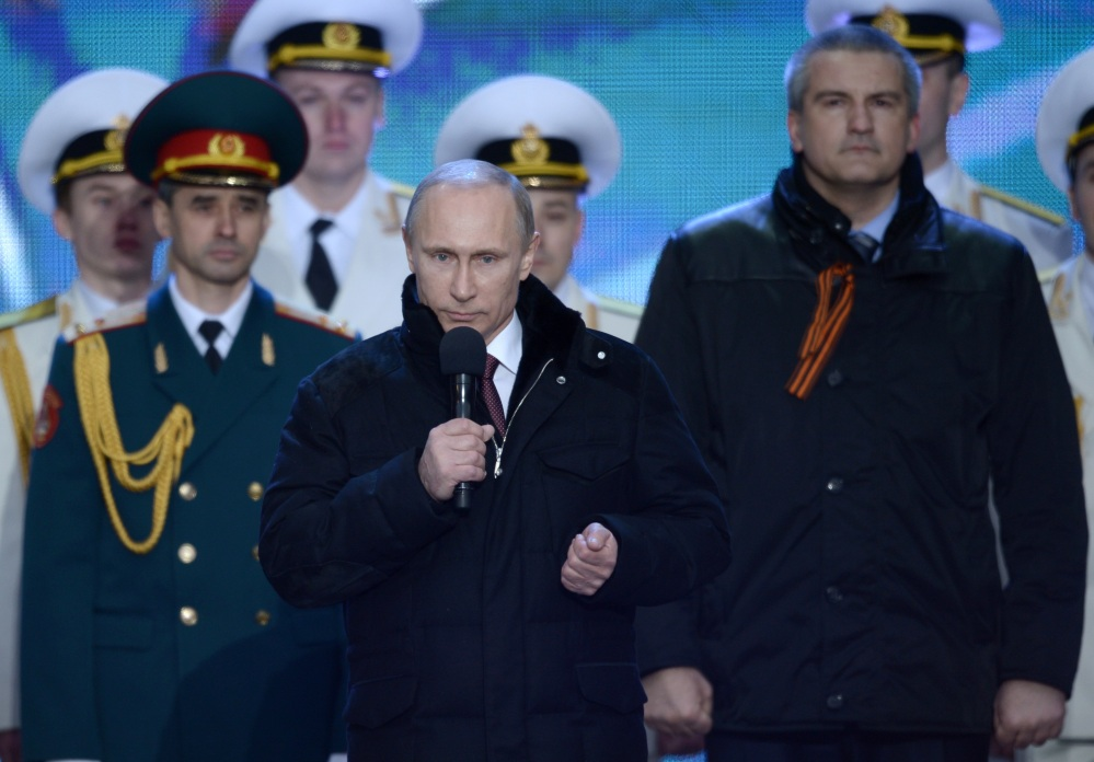 Russian President Vladimir Putin speaks at a rally in support of Crimea joining Russia, in Red Square Tuesday. With a sweep of his pen, Putin added Crimea to the map of Russia, describing the move as correcting past injustice and responding to what he called Western encroachment upon Russia's vital interests. At right is Crimean Premier Sergei Aksyonov.