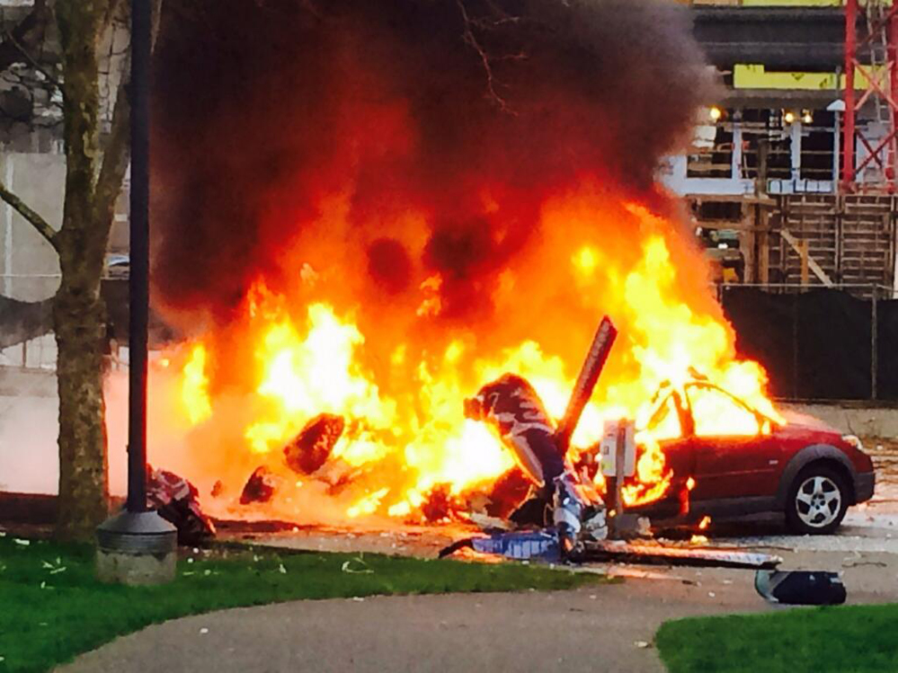 In this photo provided by KOMO-TV, a car burns at the scene of a helicopter crash outside the KOMO-TV studios near the Space Needle in Seattle on Tuesday.