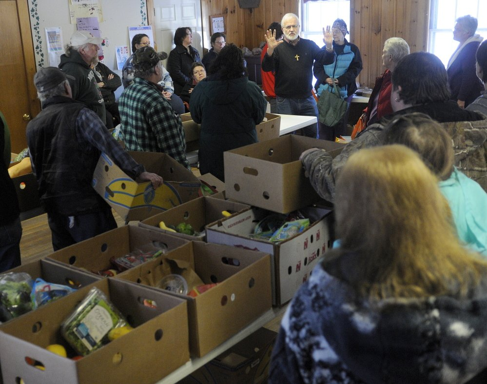 Pastor Sam Richards tells customers at the East Winthrop Baptist Church Food Ministry on Tuesday that Hannaford will no longer give to food pantries unaffiliated with Good Shepherd Food Bank.