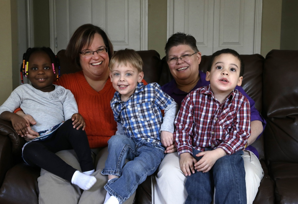 April DeBoer, second from left, and Jayne Rowse, second from right, sit with their adopted children at their home in Hazel Park, Mich. The two nurses who've been partners for eight years claimed Michigan's gay marriage ban violated their rights under the U.S. Constitution.