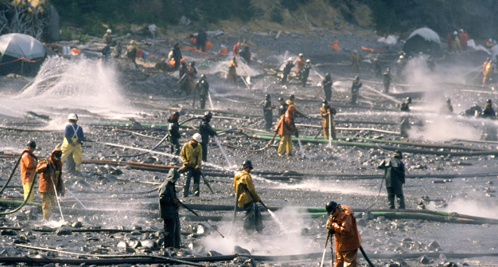 Exxon Valdez oil spill workers use high-pressure hoses to wash oil from the beach at Smith Island on Alaska's Prince William Sound in April 1989.
