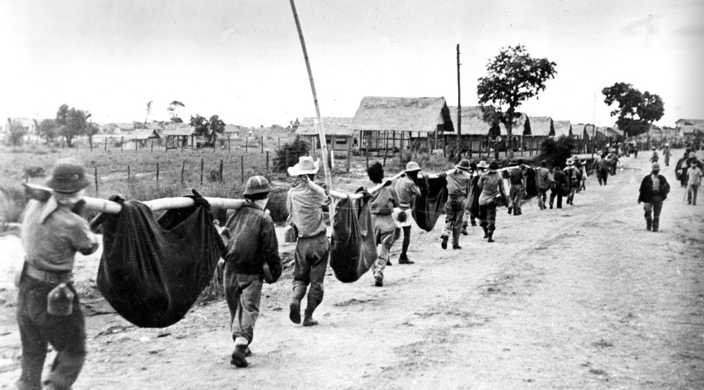Allied prisoners of war carry their comrades in slings during a burial detail. In 2009, John E. Love, a Bataan Death March survivor, joined a campaign with other Bataan Death March survivors to change the caption of this photo.