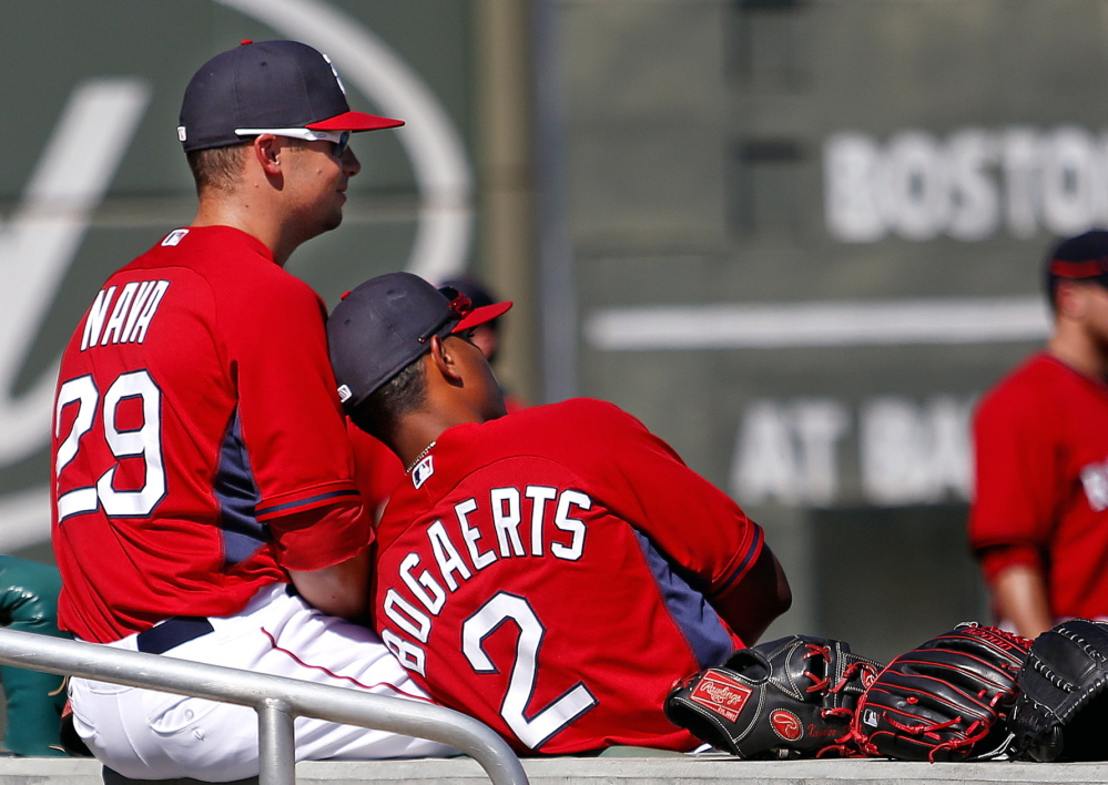 "Daniel Nava and Xander Bogaerts take a break before a spring training game at JetBlue Park last Thursday. Of last year's champions, Manager John Farrell said: ""That was the closest team I've been around in 30 years of professional baseball."""