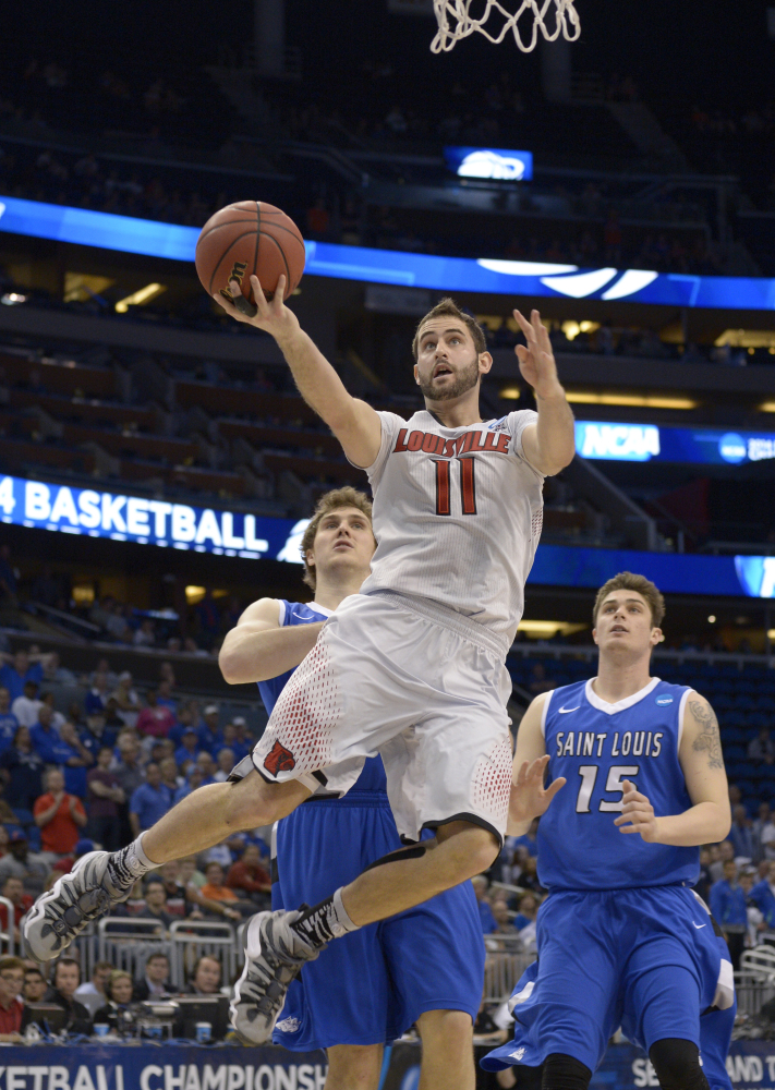 Louisville forward Luke Hancock (11) drives to the basket ahead of Saint Louis forwards Rob Loe (51) and Tanner Lancona (15), during the second half in a third-round game in the NCAA college basketball tournament Saturday.