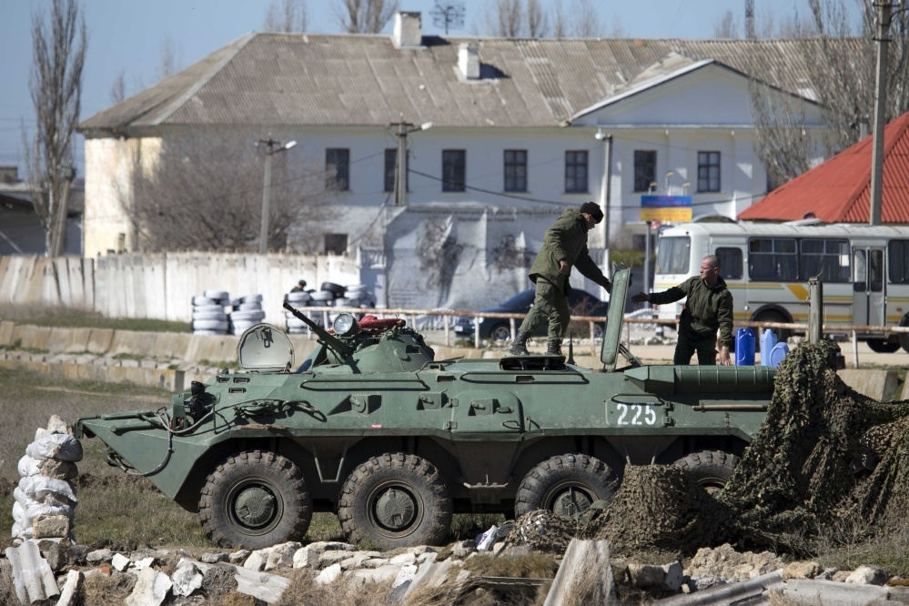 Pro-Russian soldiers in unmarked uniforms arrange a position on top an APC near Ukrainian marines base in the city of Feodosia, Crimea, on Sunday.
