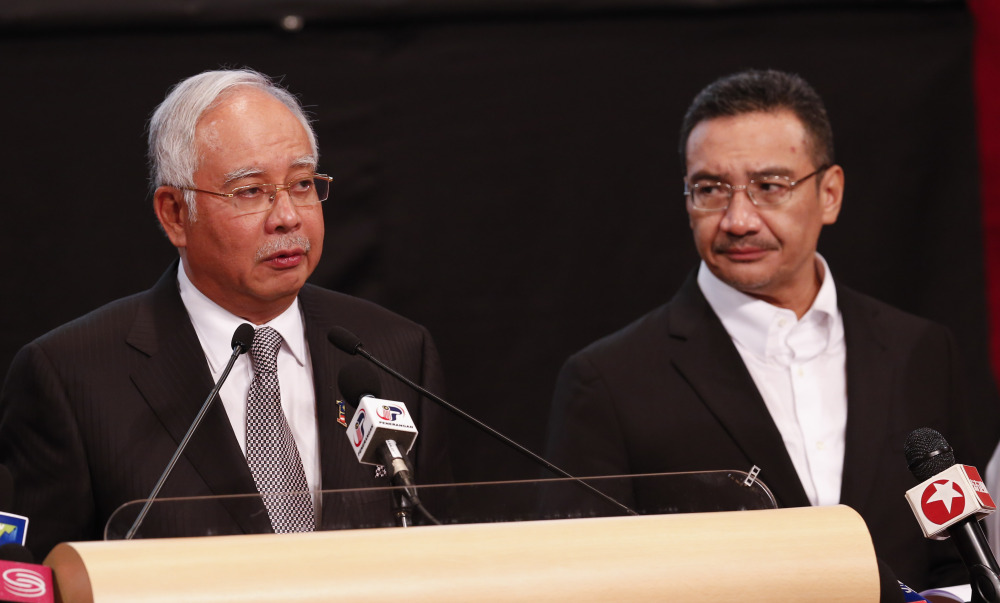 Malaysia's Prime Minister Najib Razak, left, and acting transport minister Hishammuddin Hussein speak during a press conference for the missing Malaysia Airlines jet in Kuala Lumpur, Malaysia, Monday.