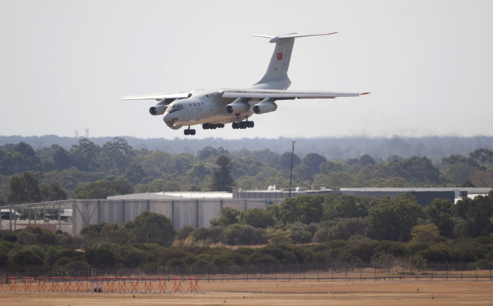 A Chinese IL-76 plane searching for the missing Malaysia Airlines Flight MH370 returns to Perth airport, Australia, after a sortie on Monday. A Chinese plane on Monday spotted two white, square-shaped objects in an area identified by satellite imagery as containing possible debris from the missing Malaysian airliner, while the United States separately prepared to send a specialized device that can locate black boxes.