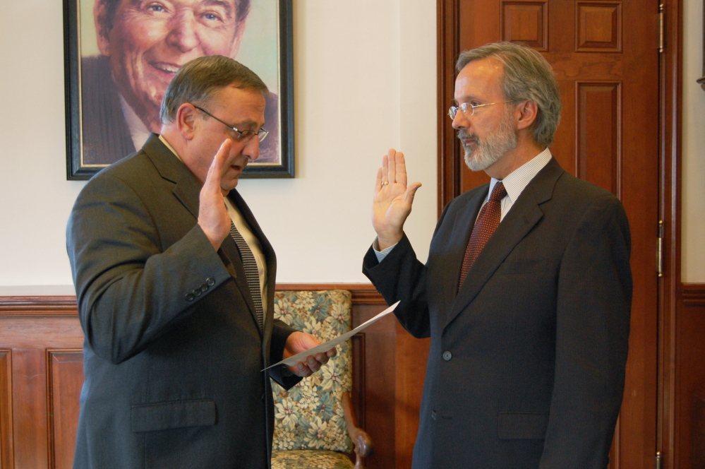 Paul H. Sighinolfi, right, is sworn in as workers' comp board executive director by Gov. Paul LePage, who ousted the previous director in 2011 after three months in office.