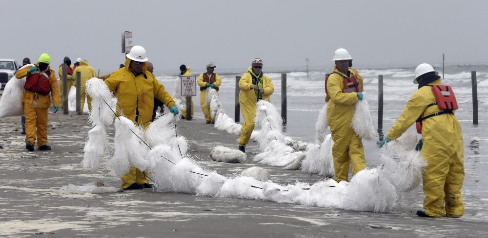 Crew members spread a viscous snare along East Beach to trap oil Monday in Galveston, Texas. Thousands of gallons of tar-like oil spilled into the major U.S. shipping channel after a barge ran into a ship Saturday.