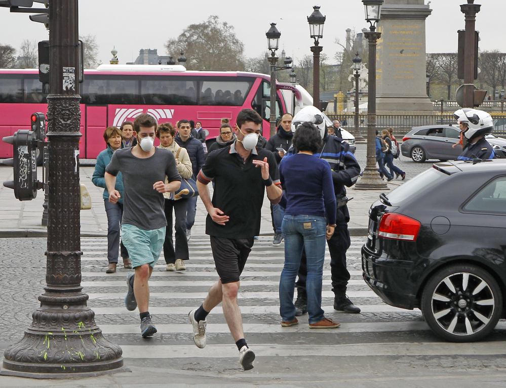 Two joggers wearing face masks run through the Place de la Concorde in Paris on Friday. Noting an increasing use of face masks in heavily polluted cities such as Beijing and Tokyo, scientists say the masks' effectiveness is unclear.