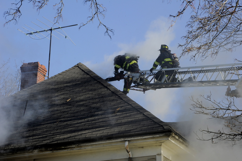 Portland firefighters probe for hotspots at 38 Columbia Road in Portland. No one was hurt in the fire.