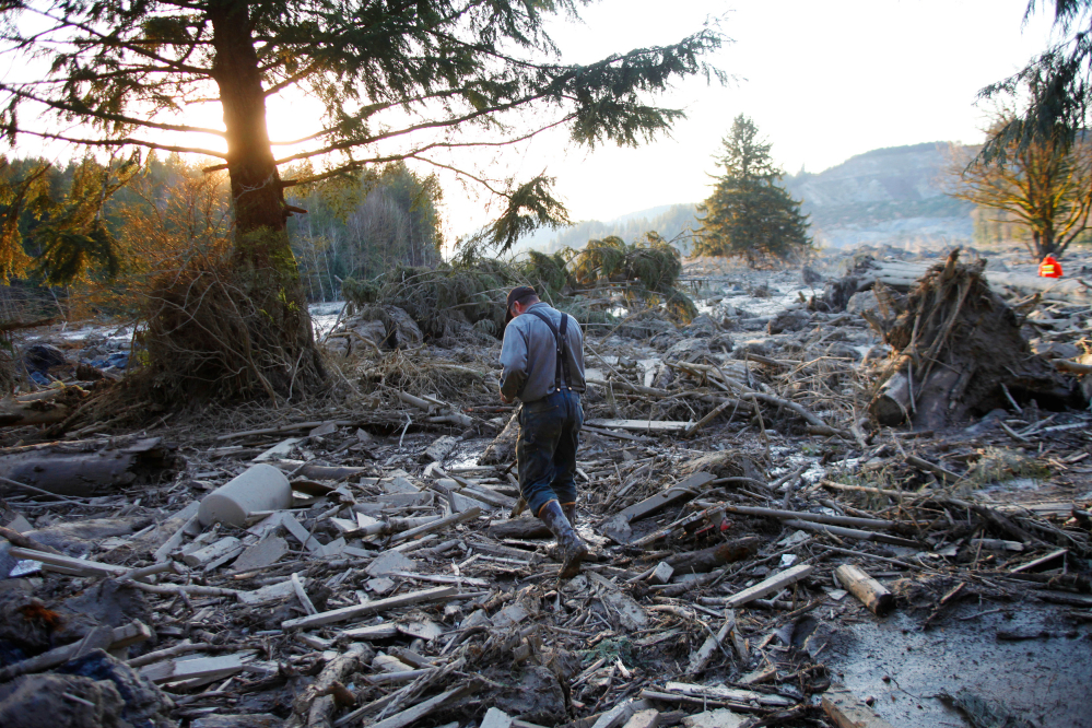 Steve Skaglund walks across the rubble on the east side of the fatal mudslide near Oso, Wash., on Sunday.